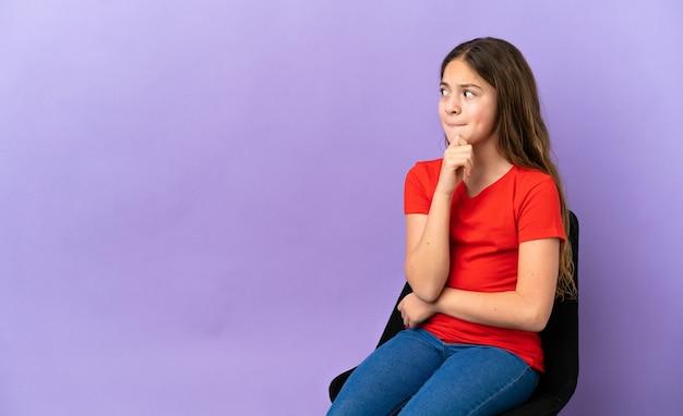 Маленькая кавказская девушка сидит на стуле, изолированном на фиолетовом фоне, сомневается и думает