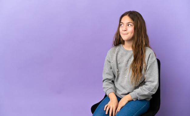 Маленькая кавказская девушка сидит на стуле, изолированном на фиолетовом фоне, сомневается, глядя вверх