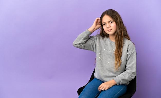 Маленькая кавказская девушка сидит на стуле, изолированном на фиолетовом фоне, сомневается