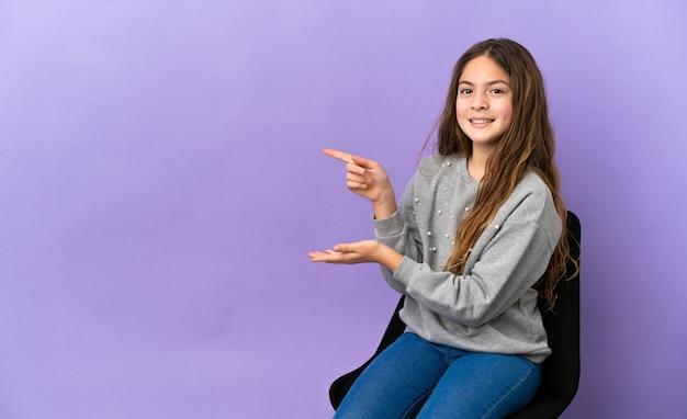 広告を挿入するために手のひらに架空のコピースペースを保持している紫色の背景に分離された椅子に座っている白人の少女