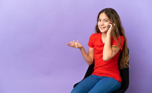 Маленькая кавказская девушка сидит на стуле, изолированном на фиолетовом фоне, разговаривает с кем-то по мобильному телефону