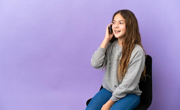 Маленькая кавказская девушка сидит на стуле, изолированном на фиолетовом фоне, разговаривает по мобильному телефону