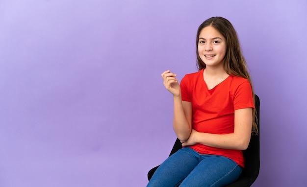 Маленькая кавказская девушка сидит на стуле, изолированном на фиолетовом фоне, смеясь