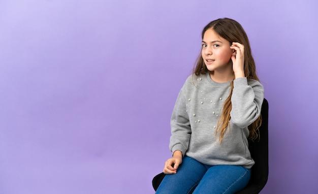 紫色の背景で隔離の椅子に座って耳に手を置くことによって何かを聞いている白人の少女