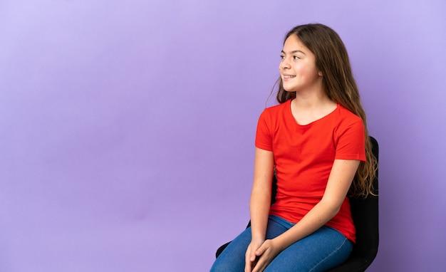 側を見て紫色の背景で隔離の椅子に座っている小さな白人の女の子