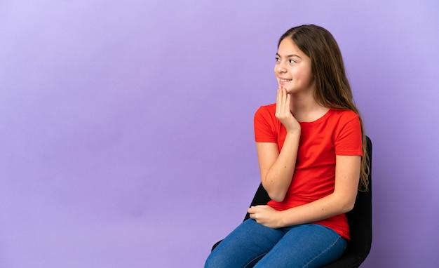 笑顔で見上げる紫色の背景で隔離の椅子に座っている小さな白人の女の子