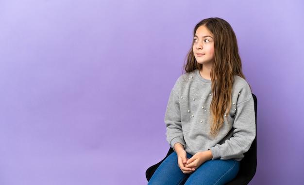 紫色の背景で隔離の椅子に座っている小さな白人の女の子は、側を見てジェスチャーを疑う