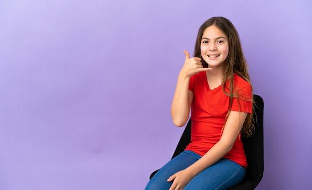 電話のジェスチャーを作る紫色の背景で隔離の椅子に座っている小さな白人の女の子。コールバックサイン