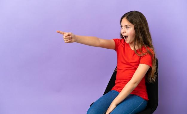 離れて指している紫色の背景で隔離の椅子に座っている小さな白人の女の子