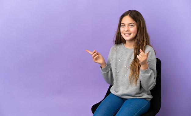 側面に指を指し、幸せな紫色の背景で隔離の椅子に座っている小さな白人の女の子