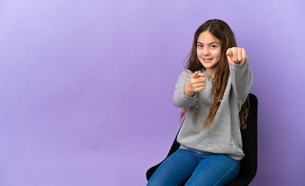 幸せな表情で正面を指す紫色の背景に分離された椅子に座っている小さな白人の女の子