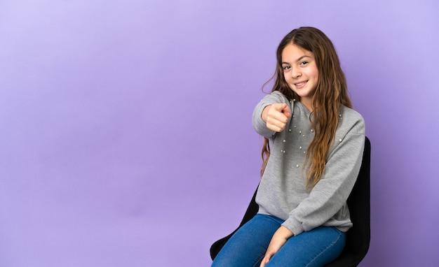 행복한 표정으로 앞을 가리키는 보라색 배경에 격리된 의자에 앉아 있는 백인 소녀