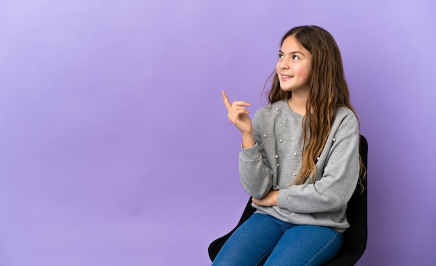 素晴らしいアイデアを指している紫色の背景に分離された椅子に座っている小さな白人の女の子