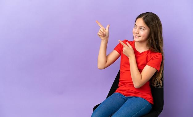 검지 손가락으로 가리키는 보라색 배경에 격리된 의자에 앉아 있는 백인 소녀