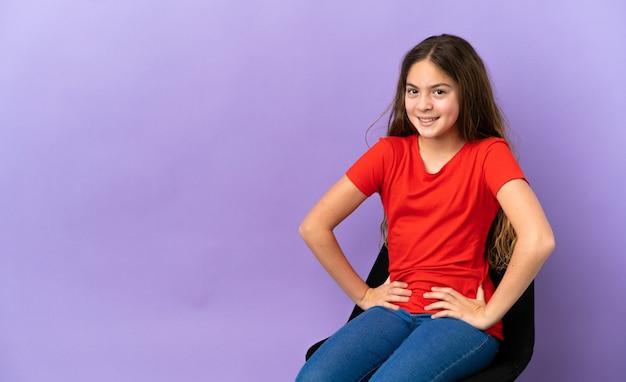 Маленькая кавказская девушка сидит на стуле, изолированном на фиолетовом фоне, позирует с руками на бедрах и улыбается