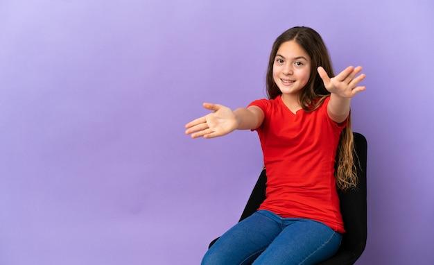 紫色の背景で隔離の椅子に座っている白人の少女は、手で来るように提示し、招待します