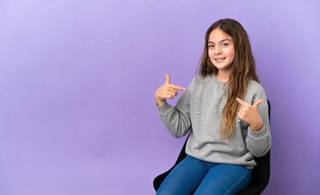 誇らしげで自己満足の紫色の背景で隔離の椅子に座っている小さな白人の女の子