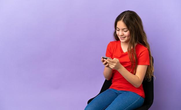 Маленькая кавказская девушка сидит на стуле, изолированном на фиолетовом фоне, отправляет сообщение с мобильного телефона