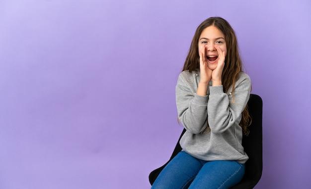 Маленькая кавказская девушка сидит на стуле, изолированном на фиолетовом фоне, кричит и что-то объявляет