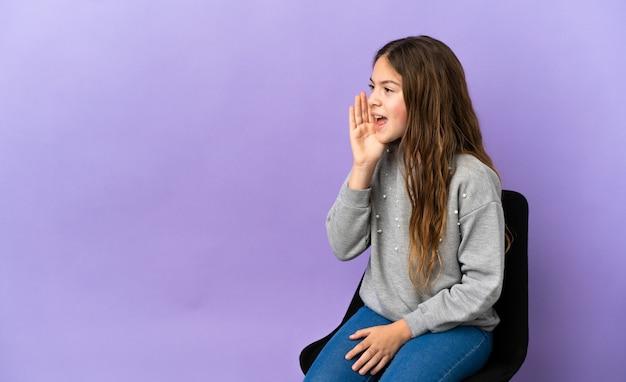 横に大きく開いた口で叫んで紫色の背景に分離された椅子に座っている小さな白人の女の子
