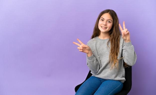 両手で勝利のサインを示す紫色の背景で隔離の椅子に座っている小さな白人の女の子