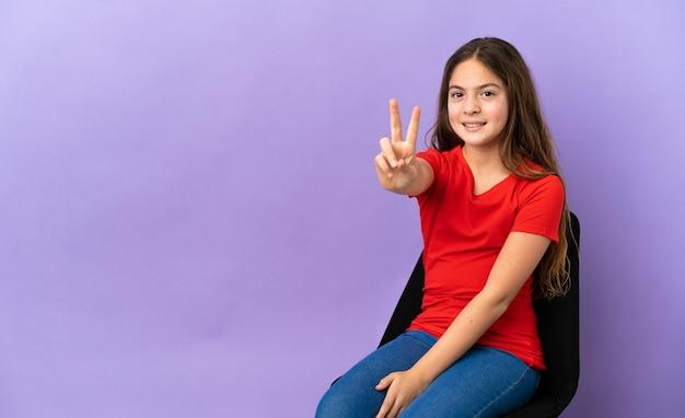 Маленькая кавказская девушка сидит на стуле, изолированном на фиолетовом фоне, улыбается и показывает знак победы
