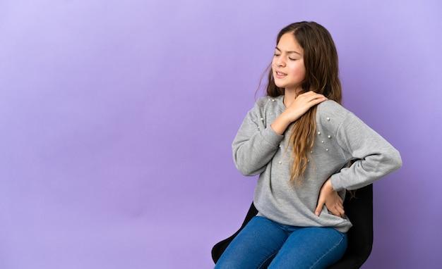 努力をしたために肩の痛みに苦しんで紫色の背景で隔離の椅子に座っている小さな白人の女の子