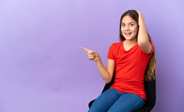 紫色の背景で隔離の椅子に座っている小さな白人の女の子は驚いて、人差し指を横に向けています