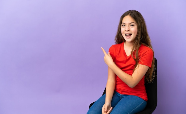 紫色の背景に分離された椅子に座っている小さな白人の女の子は驚いて、側を指しています