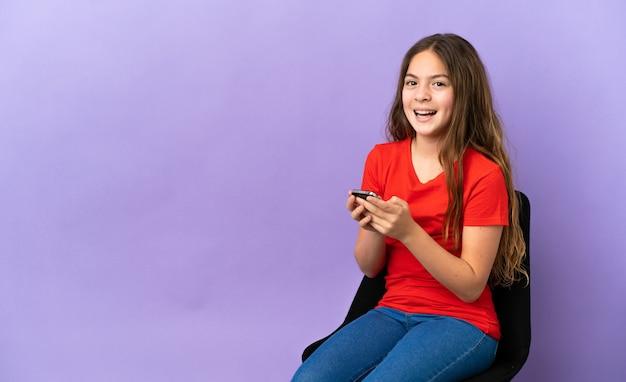 紫色の背景で隔離の椅子に座っている小さな白人の女の子は驚いてメッセージを送信します
