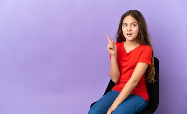 紫色の背景で隔離の椅子に座っている小さな白人の女の子は、指を上に向けるアイデアを考えています