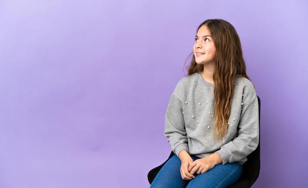 見上げながらアイデアを考えて紫色の背景で隔離の椅子に座っている小さな白人の女の子