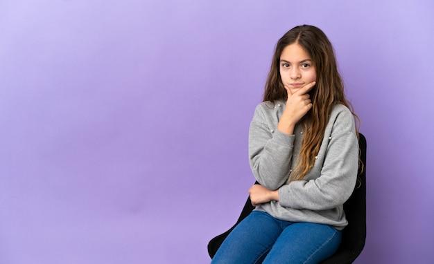 紫色の背景思考で隔離の椅子に座っている小さな白人の女の子