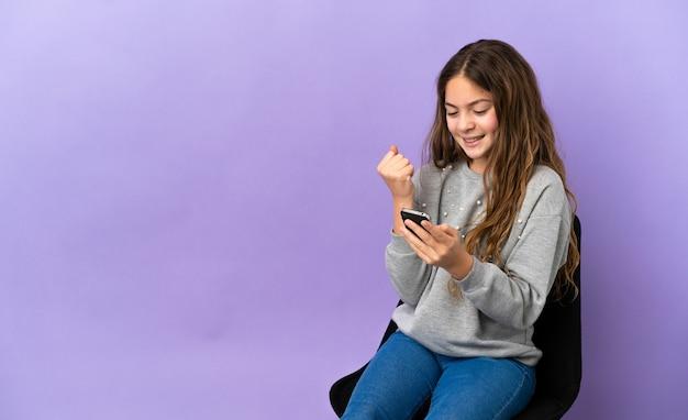 Маленькая кавказская девушка сидит на стуле, изолированном на фиолетовом фоне с телефоном в позиции победы Premium Фотографии