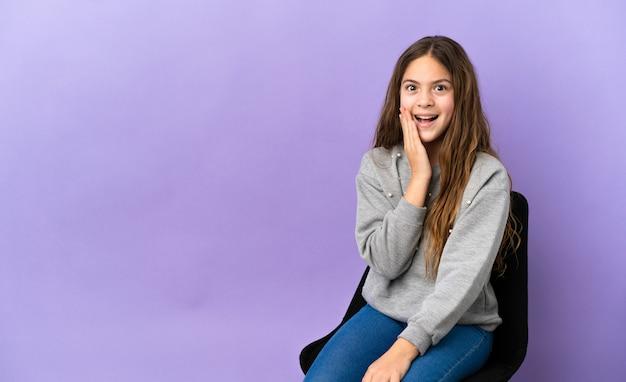 Маленькая кавказская девушка сидит на стуле, изолированном на фиолетовом фоне, с удивленным и шокированным выражением лица