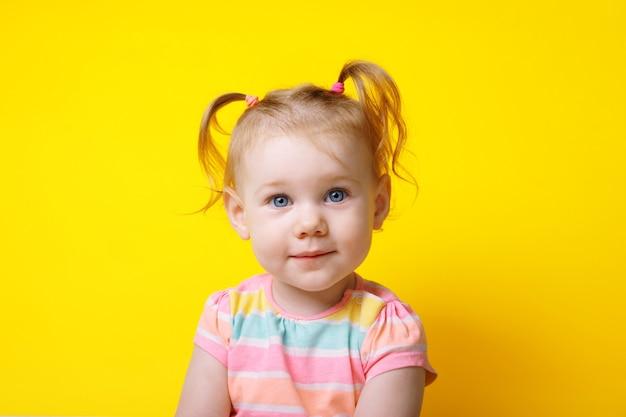 노란색 배경 위에 카메라를 보고 웃고 있는 백인 소녀