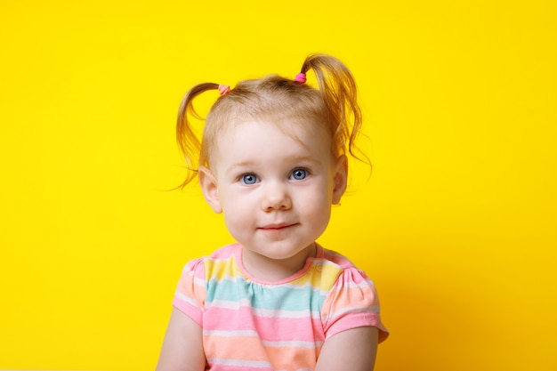 Little caucasian girl smiling and looking at the camera over yellow background