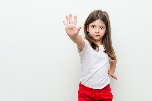 Little caucasian girl standing with outstretched hand showing stop sign, preventing you.