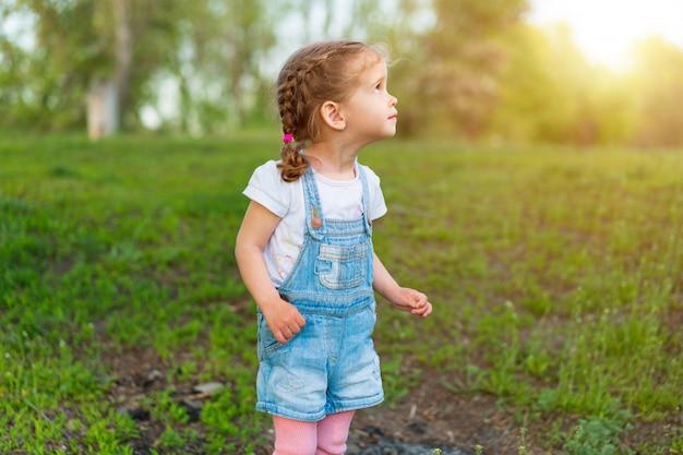 Little caucasian girl walks on nature dressed in denim overalls