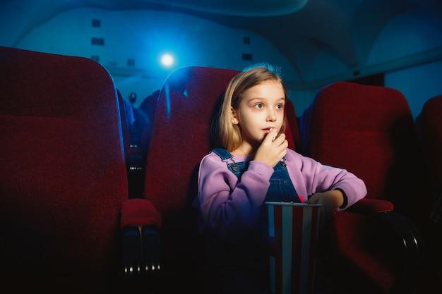 Маленькая кавказская девочка смотрит фильм в кинотеатре, доме или кино.