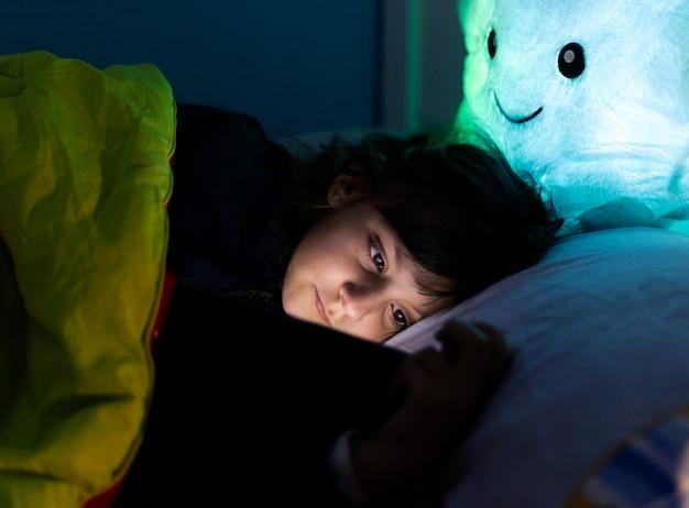 Маленькая кавказская девочка смотрит планшет в постели перед сном