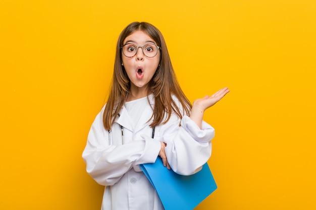 医師の衣装を着ている白人少女は、手のひらにコピースペースを保持して感銘を受けました。
