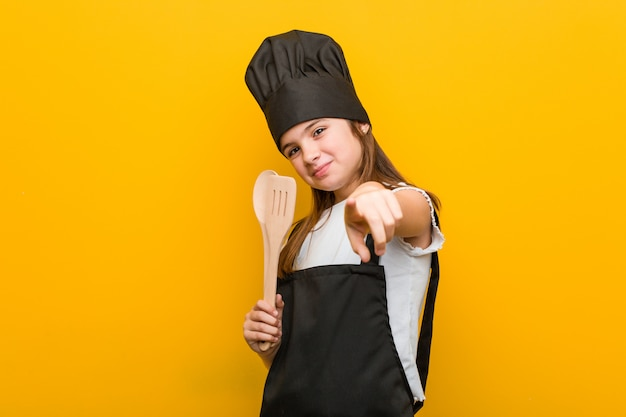 Little caucasian girl wearing a chef costume cheerful smiles pointing to front.