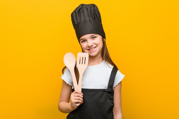 Little caucasian girl wearing a chef costume happy, smiling and cheerful.