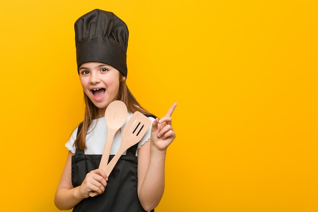 Little caucasian girl wearing a chef costume smiling cheerfully pointing with forefinger away.