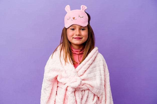 幸せ、笑顔、陽気な紫色の背景に分離されたパジャマを着ている小さな白人の女の子。