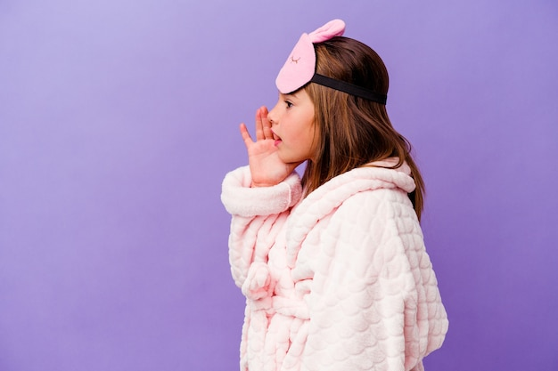 Little caucasian girl wearing pajama isolated on purple background shouting and holding palm near opened mouth.