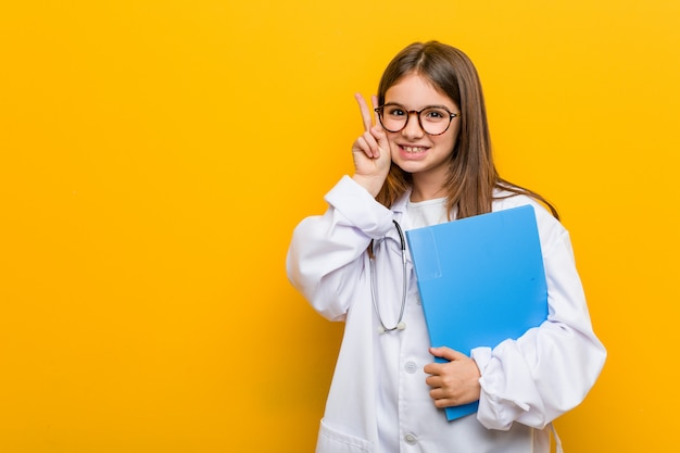 Little caucasian girl wearingdoctor costume smiling and raising thumb up