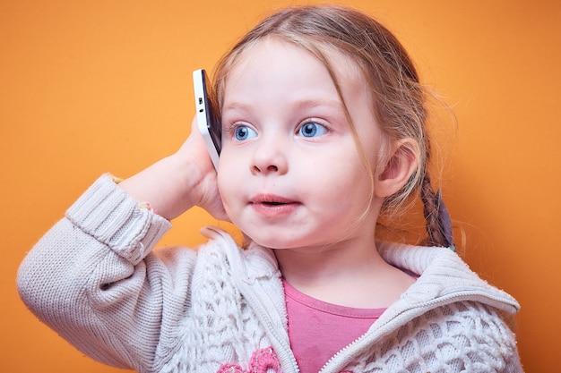 Маленькая кавказская девочка с телефоном в руке на цветном