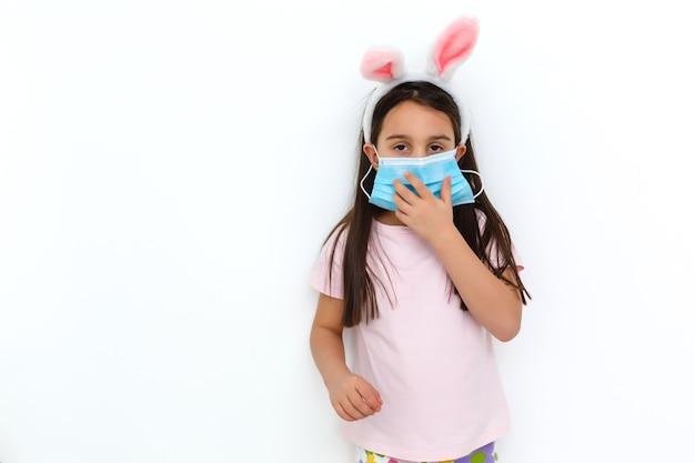 토끼 귀와 흰색 배경에 그녀의 얼굴에 의료 마스크를 쓴 백인 소녀. 부활절 개념입니다. 코로나바이러스 보호